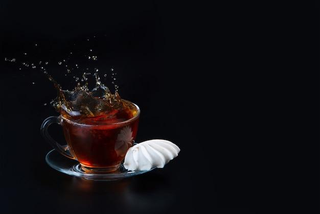 Filiżanka czarnej herbaty na czarnej powierzchni odizolowane