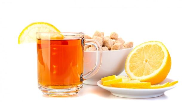 Filiżanka czarnej herbaty z cytryną, cytryna na spodku, brązowy cukier.