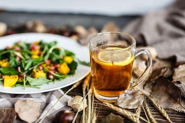 Filiżanka czarnej herbaty z cytryną i sałatką z mango, nasiona granatu na białym talerzu