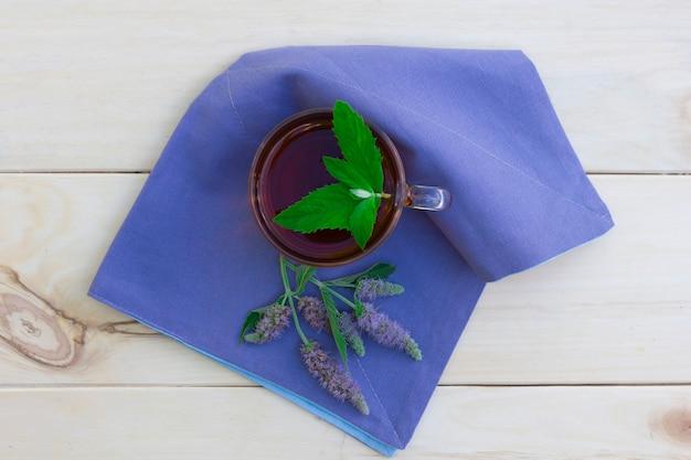 Filiżanka czarnej herbaty z gałązką mięty i kwiatów mięty na drewnianym stole