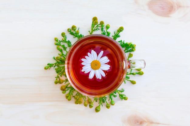 Filiżanka czarnej herbaty ziołowej z gałązkami, kwiaty rumianku aptecznego na drewnianym stole