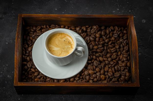 Filiżanka czarnej kawy i palonych ziaren kawy w drewnianym pudełku.
