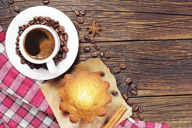 Filiżanka czarnej kawy i słodkie ciastko na drewnianym obrusie na obrus