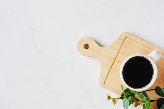 Filiżanka czarnej kawy i sztuczny roślina wystrój na drewnianej tacy przeciw