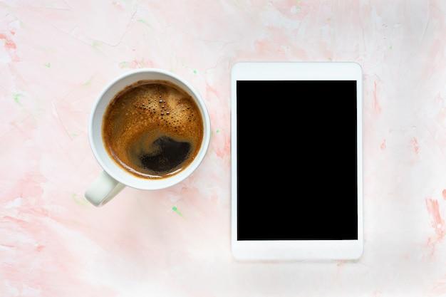 Filiżanka czarnej kawy i tablet na jasnoróżowej ścianie rustykalne. leżał z płaskim, widok z góry, miejsce, szablon mediów społecznościowych, koncepcja rano i internet