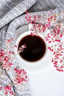 Filiżanka czarnej kawy na białym tle sweter i jasne różowe kwiaty. leżał płasko. skopiuj miejsce. koncepcja mody. przytulny styl życia. martwa natura