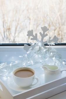 Filiżanka czarnej kawy na parapecie zimowym z girlandą