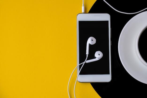 Filiżanka czarnej kawy na płycie winylowej. skopiuj miejsce. słuchać muzyki. styl retro. podcast. telefon komórkowy ze słuchawkami.
