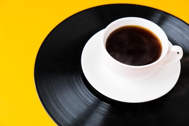 Filiżanka czarnej kawy na płycie winylowej. skopiuj miejsce. słuchać muzyki. styl retro. podcast.