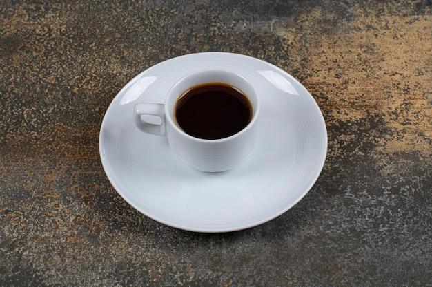 Filiżanka czarnej kawy na powierzchni marmuru.