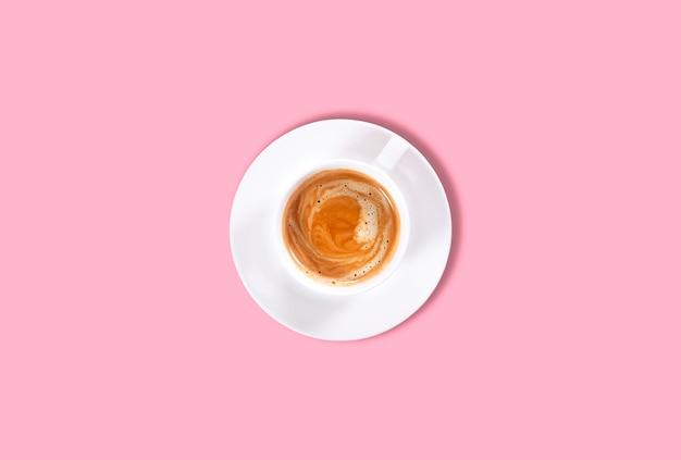 Filiżanka czarnej kawy na różowym tle. widok z góry. twardy cień.