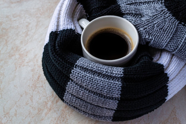 Filiżanka czarnej kawy owinięta szalikiem w paski. koncepcja księżyca jesienią i zimą.