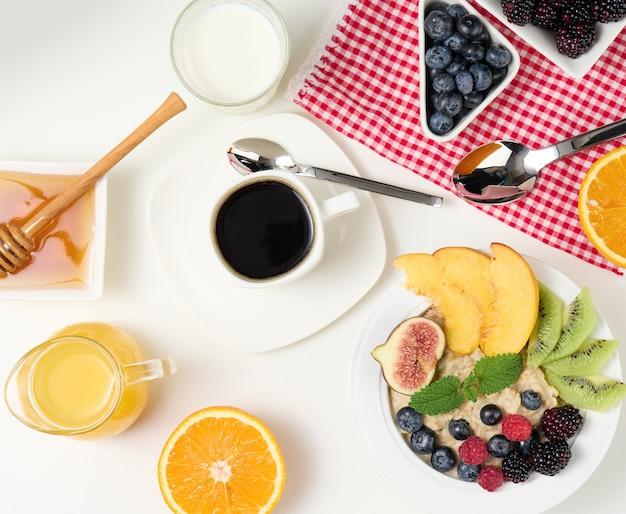 Filiżanka czarnej kawy, talerz płatków owsianych i owoców, miód i szklanka mleka na białym stole, zdrowe poranne śniadanie, widok z góry