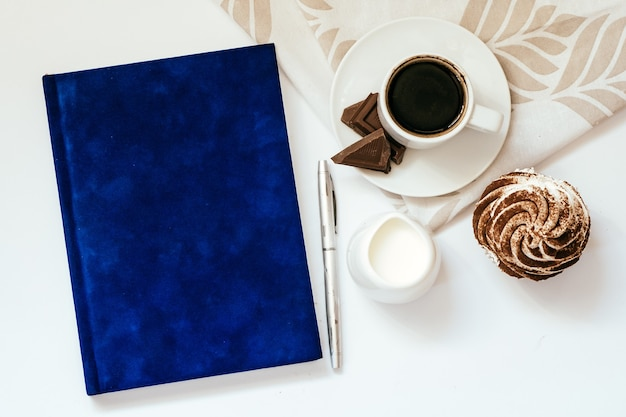 Filiżanka czarnej kawy z czekoladą i babeczkami oraz niebieski notatnik