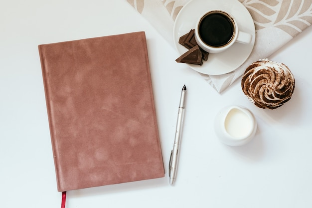 Filiżanka czarnej kawy z czekoladą i babeczkami oraz notatnik