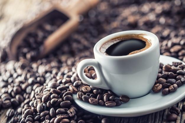 Filiżanka czarnej kawy z fasolą na drewnianym stole.