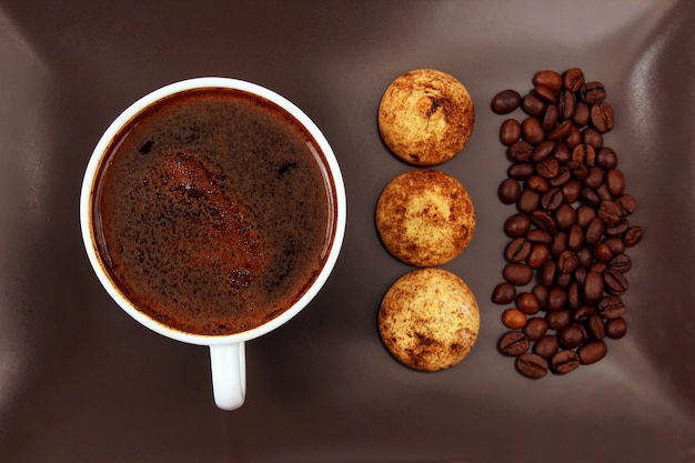 Filiżanka czarnej kawy z herbatnikami i fasolą na ciemnym talerzu