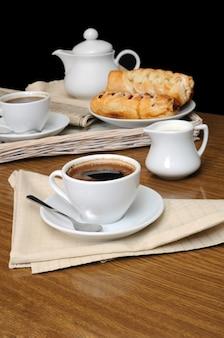 Filiżanka czarnej kawy z mleczarzem z ciastami na tacy z gazetą