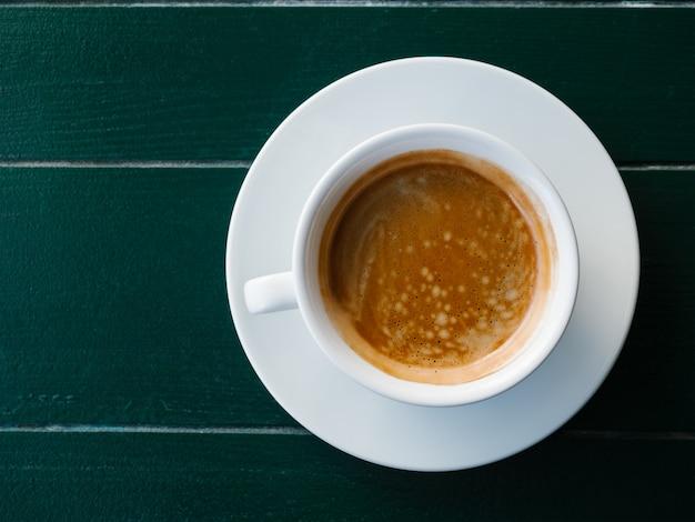 Filiżanka czarnej kawy z pianką na szmaragdowym drewnianym tle espresso lub americanoe