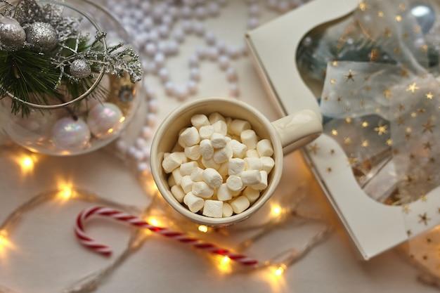 Filiżanka czekolady z piankami, ozdoby świąteczne na białym stole, laska cukrowa i pudełko upominkowe