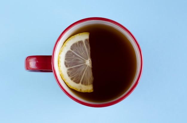 Filiżanka czerwonej herbaty z kompozycją plasterka cytryny