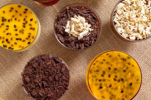 Filiżanka deseru z musem z mlecznej czekolady i wiórkami z białej czekolady, musem ganache i musem z marakui.