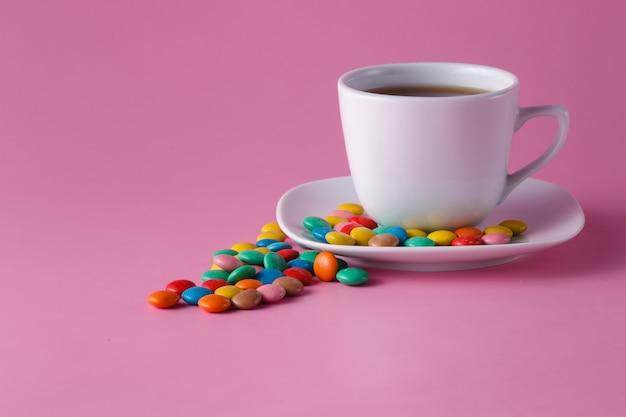 Filiżanka do herbaty z kolorowymi słodkimi drażetkami na spodku