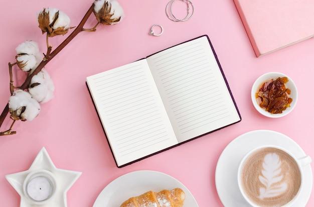 Filiżanka do kawy i notatnik z rogalikiem i bawełnianą gałązką