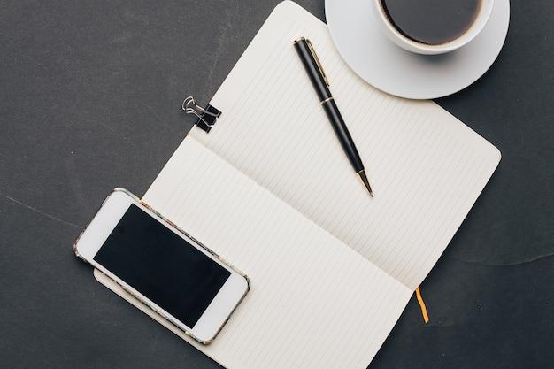 Filiżanka do kawy na stole notatnik z technologią długopisu