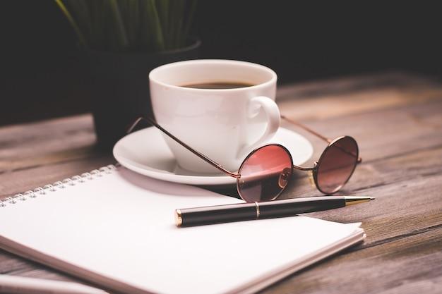 Filiżanka do kawy, papierowe, notatnik, praca, drewniany stół, kwiat doniczkowy