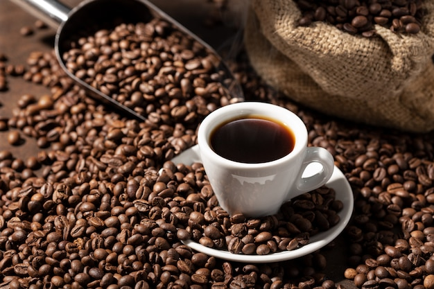 Filiżanka espresso kawa i palone ziarna. kawa w tle