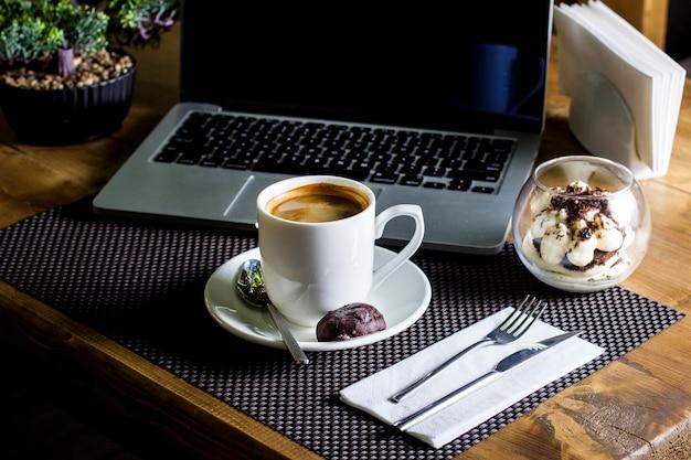 Filiżanka espresso podawana z tiramisu w szklanej misce