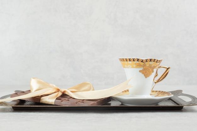 Filiżanka espresso z tabliczką czekolady przewiązana wstążką na tacy.