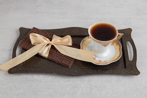 Filiżanka espresso z tabliczką czekolady przewiązana wstążką na tacy