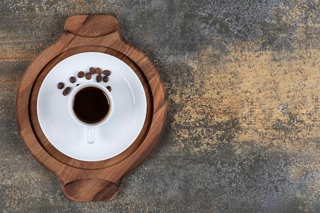 Filiżanka espresso z ziaren kawy na desce.