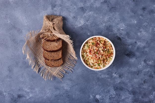 Filiżanka fasoli podawana z kromkami chleba.