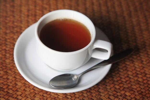 Filiżanka gorąca herbata dalej wyplata drewnianego stołowego tło