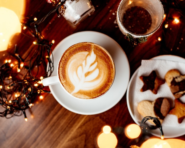 Filiżanka gorącego cappuccino i talerz z ciastka odgórnym widokiem