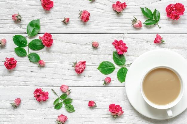Filiżanka gorącego cappuccino lub kawy z mlekiem na białym spodku z kompozycją kwiatów wykonanych z różowych kwiatów róży