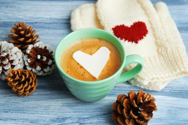 Filiżanka gorącego cappuccino z pianką w sercu, ciepłymi rękawiczkami i sosnowymi szyszkami