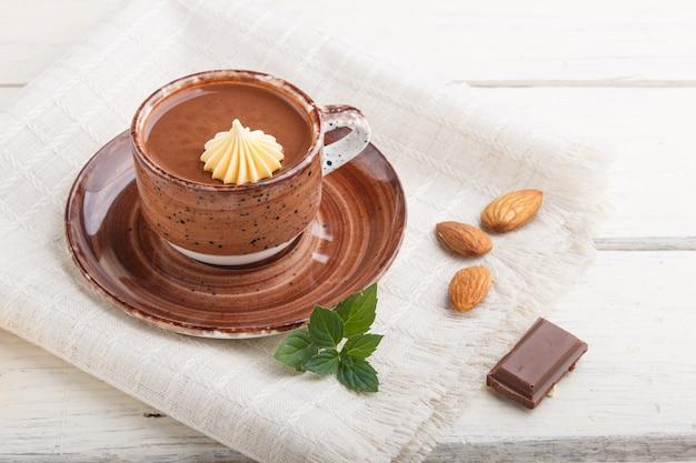 Filiżanka gorącej czekolady i kawałków mlecznej czekolady z migdałami na białej drewnianej powierzchni z lnianą serwetką. widok z boku