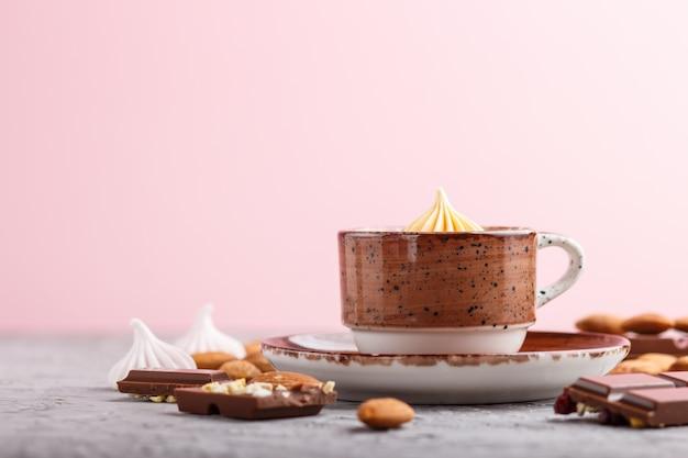 Filiżanka gorącej czekolady i kawałków mlecznej czekolady z migdałami na szaro-różowej ścianie. widok z boku, selektywne focus.
