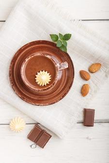 Filiżanka gorącej czekolady i kawałków mlecznej czekolady z migdałami