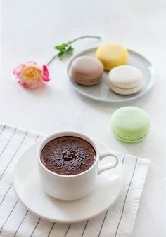Filiżanka gorącej czekolady z kwiatami macarons