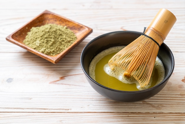Filiżanka gorącej herbaty matcha z zieloną herbatą w proszku i bambusową trzepaczką
