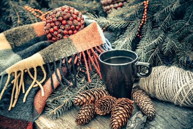Filiżanka gorącej herbaty na nieociosanym drewnianym stole. martwa natura z szyszek, gałęzi jodłowych. przygotowanie do świąt bożego narodzenia.