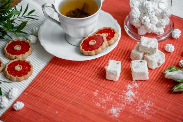 Filiżanka gorącej herbaty owocowej i świąteczne pierniczki na tacy z anyżem i orzechami laskowymi.