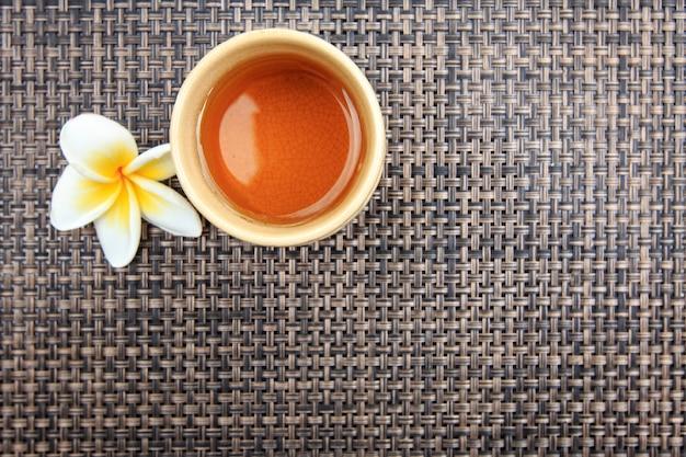 Filiżanka gorącej herbaty z kwiatem frangipani na macie bambusowej