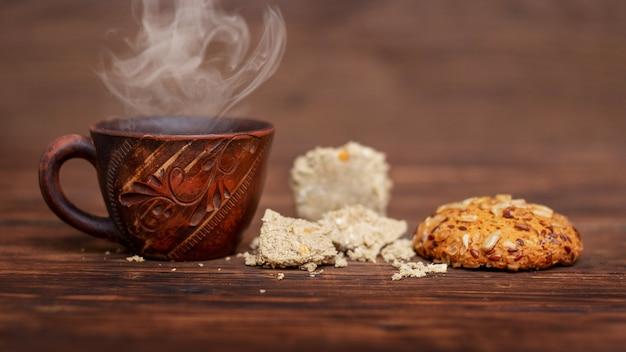 Filiżanka gorącej kawy, ciastek i chałwy na drewnianym stole