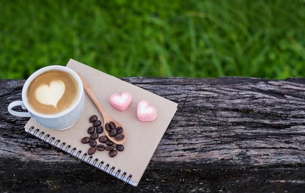 Filiżanka gorącej kawy do porannego drinka ze słodkimi cukierkami serca. relaks i wolność z naturalnym tłem. skopiuj miejsce na tekst